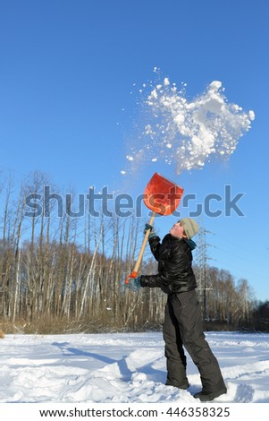 boy in clearing in winter woods vigorously tosses snow shovel - stock photo