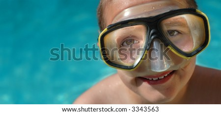 Boy in diving mask on a hot summer day; horizontal banner with plenty of space for copy