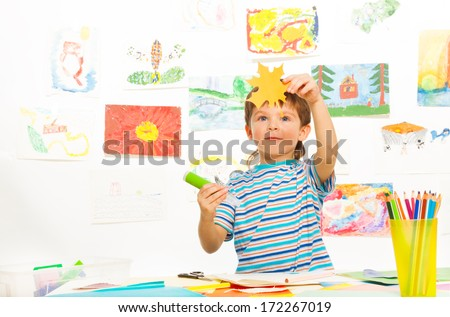 Boy in early development class cut paper and glue holding paper maple leaf and glue stick - stock photo
