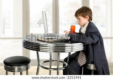 Boy in father's suit at table with soda and laptop. - stock photo