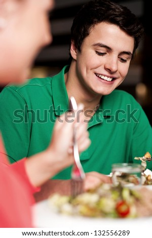 Boy in focus enjoying his meal. Having great time. Blur image of a woman too. - stock photo