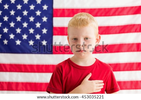 Boy in front of American flag with hand over heart - stock photo