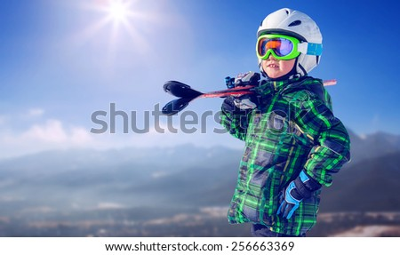 Boy in full ski equipment on the mountain view - stock photo