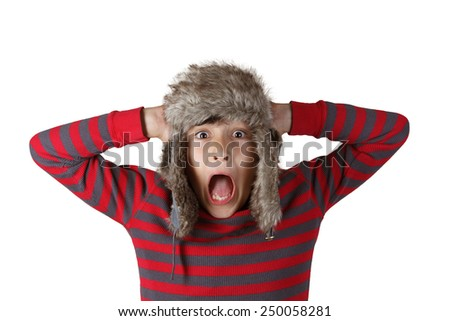 Boy in furry hat pulling funny faces on white background - stock photo