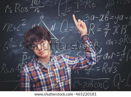 Boy in glasses, blackboard filled with math formulas background, retro toned