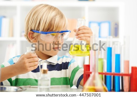 Boy in goggles holding flask with chemical reagent - stock photo