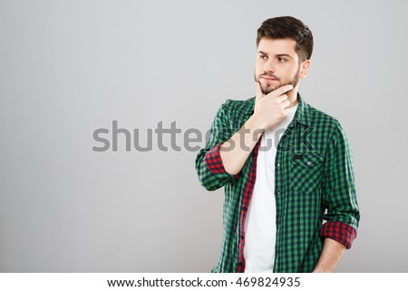 Boy in green checked T-shirt. Young man, clothing, casual style. Thinking about something, thoughtful, looking aside. Waist up. Indoors, studio