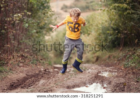 Boy in gumboots jumps into the puddle - stock photo