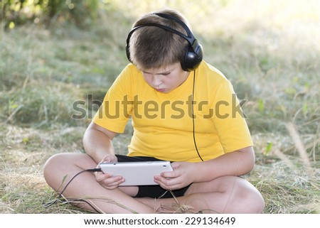 Boy in headphones looking at tablet computer on the nature