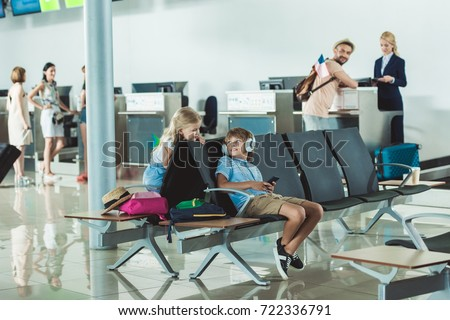 boy in headphones using smartphone with sister near by and father at check in desk at airport