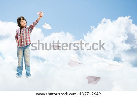 Boy in helmet pilot launches paper airplanes in the clouds - stock photo
