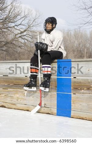 Boy in ice hockey uniform holding hockey stick sitting on sidelines. - stock photo