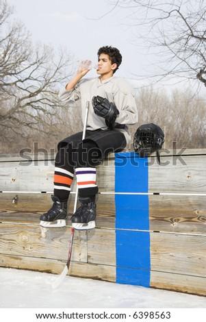 Boy in ice hockey uniform holding hockey stick sitting on sidelines drinking water. - stock photo