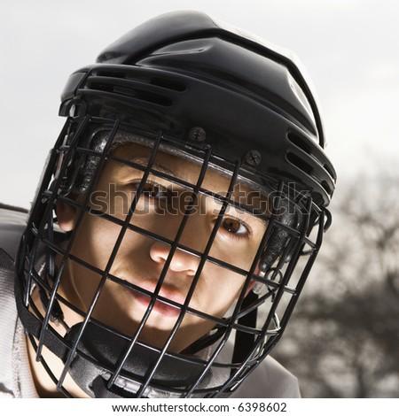 Boy in ice hockey uniform making eye contact. - stock photo