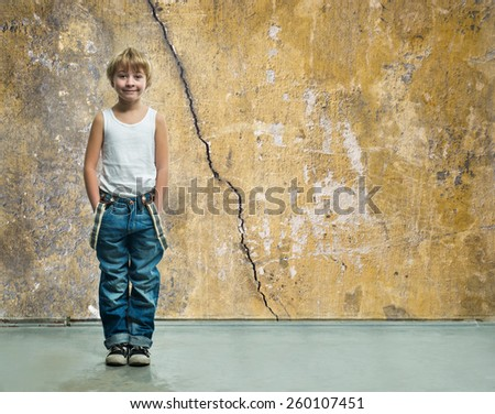 Boy in jeans stands near a wall - stock photo