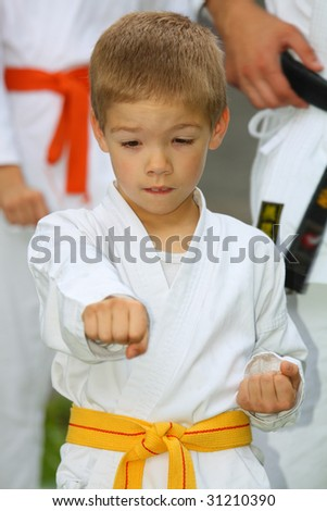 boy in karate suit with yellow belt training - stock photo