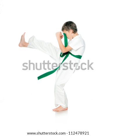 Boy in kimono with green belt practising  on a white background - stock photo