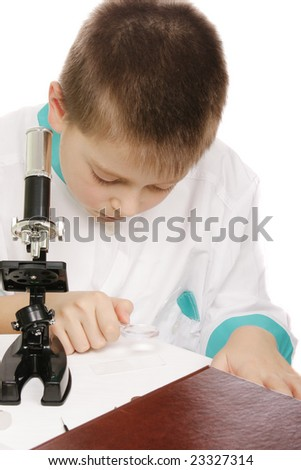 Boy in lab smock using magnifier for examination - stock photo