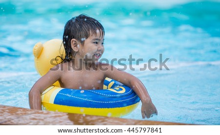 Boy in life ring on an inflatable circle in the pool. A child in the pool - stock photo