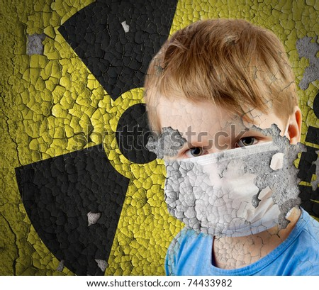 Boy in mask over old Sign of radiation on the concrete grunge station's wall with peeling paint background. - stock photo