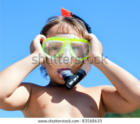 Boy in mask with a tube for diving on blue bright sky