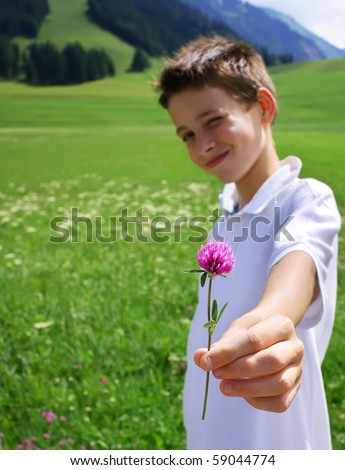 Boy in mountainous environment giving wild flower. - stock photo