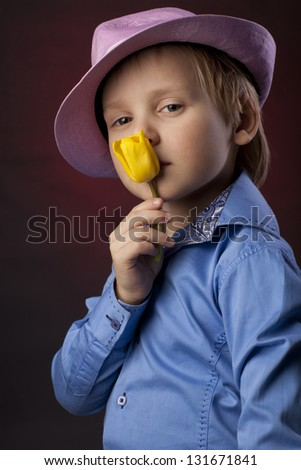 boy in pink hat smells yellow tulips