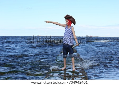 Boy in pirate hat and with spyglass points his hand to distance standing among the sea waves - romance of piracy and distant wanderings