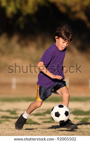 Boy in purple shirt plays soccer in the late afternoon sunlight - stock photo