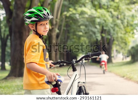 Boy in safe helmet with bicycle in city park - stock photo