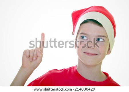 boy in Santa hat pointing up using his index finger over white - stock photo
