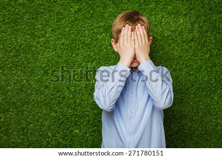 Boy in shirt  hiding his eyes over green grass