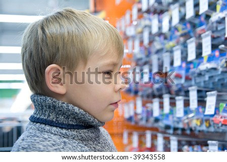 Boy in shop with toys - stock photo