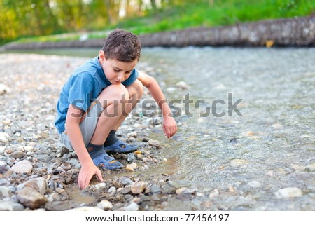 Boy in shorts, t-shirt and slippers playing with pebbles on a river bank - stock photo