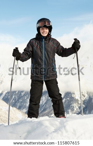Boy in ski suit stands leaning on ski poles with blue sky and mountains on background - stock photo
