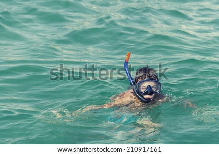 Boy in snorkeling mask with snorkel at sea, ocean green water, VINTAGE - stock photo