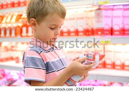 Boy in store with milk - stock photo