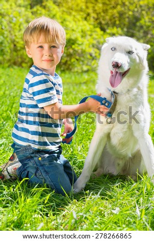 boy in striped T-shirt sitting on grass and holding leash dog in park