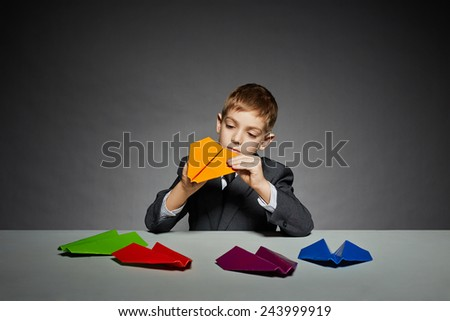 Boy in suit making yellow paper plane - stock photo