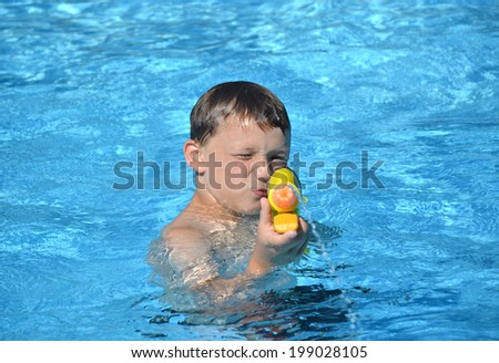 boy in swimming pool playing with water gun - stock photo