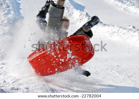 boy in the air while sledding fast down the hill with snow background - stock photo