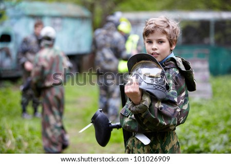 Boy in the camouflage holds a paintball gun barrel up in one hand and protective helmet in another, standing halfturned on the paintball ground with group of players on the background. - stock photo