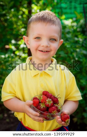 boy in the garden with strawberries