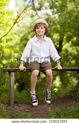 Boy in the hat and shorts sitting on a bench and smiling - stock photo