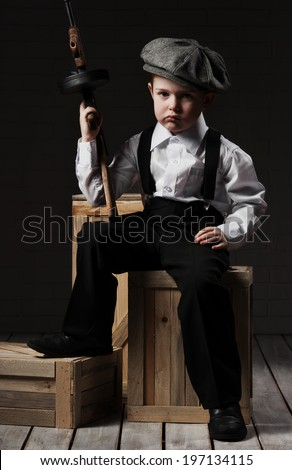 Boy in the image of gangster with gun sitting on boxes in stock - stock photo