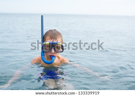 Boy in the sea wearing a mask for diving in sunny day. - stock photo