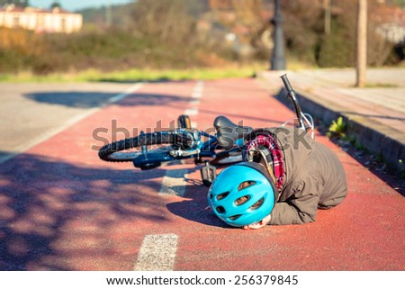 Boy in the street ground touching his head protected with a helmet after falling off to his bicycle - stock photo
