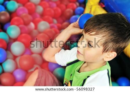 boy in the theme-park having fun in ball pool - stock photo