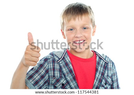 Boy in trendy clothes looking at the camera and showing thumbs up sign