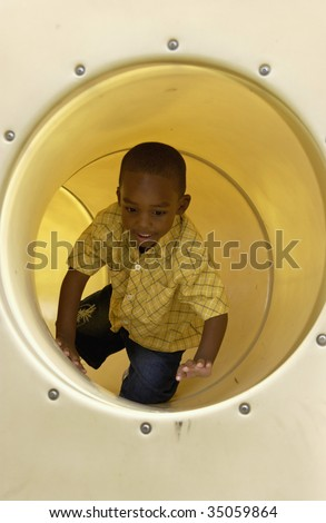 boy in tube on playground - stock photo